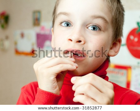 Boy holding lost deciduous teeth against his drawing on the wall