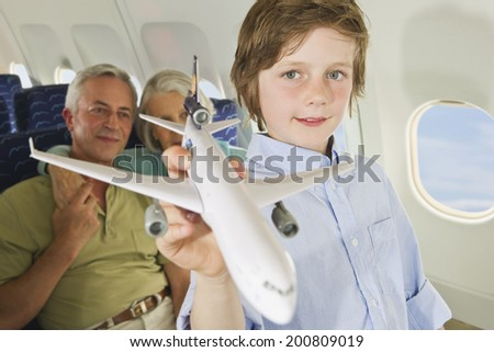 Boy holding model airplane with senior man and woman on airplane