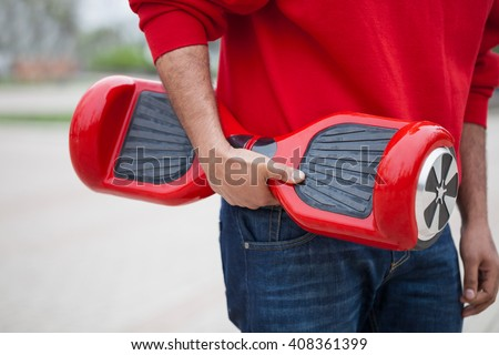 Boy holding modern red electric mini segway or hover board scooter in hands.Trending new transportation technology that produces no air pollution to the atmosphere.African male model, focus on device - stock photo