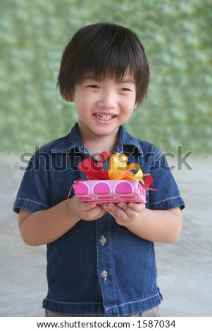 boy holding present wrapped with red & yellow ribbon - stock photo