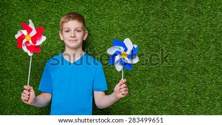 Boy holding red white and blue pinwheels over green grass
