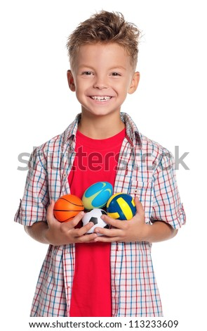 Boy holding small volleyball, rugby, basketball and soccer balls in hands isolated on white background - stock photo