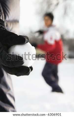 Boy holding snowball ready to throw at boy in background. - stock photo