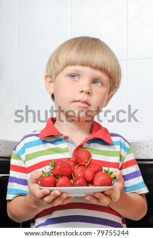 boy holds a plate with strawberries