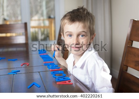 Boy home learning with letter in the kitchen table