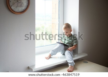 boy home sits on the window sill in the green shirt and the pants play looks tablet cartoons games movies movie