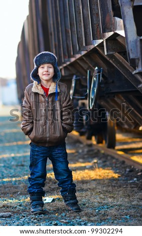 Boy homeless bum in a brown jacket and a fur hat and crumpled jeans on the street near railway wagon
