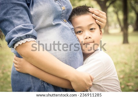 Boy hug the belly of his pregnant mother. - stock photo