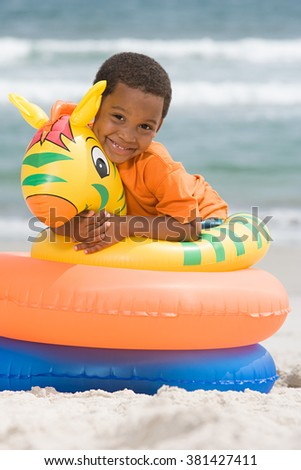 Boy hugging inflatable ring - stock photo