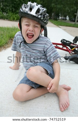 Boy hurt after falling off his bicycle - stock photo