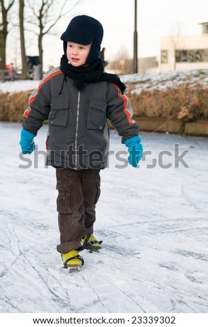 Boy ice skating for the first time - stock photo