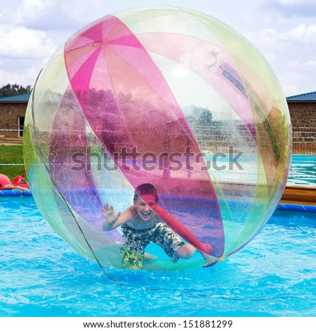 Boy in a ball on the water. Water Zorbing - stock photo