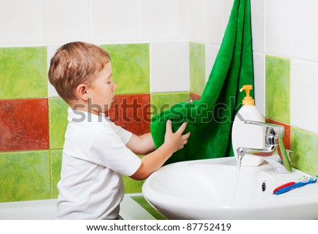 boy in a bathroom wipes the washed up hands a towel