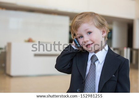 Boy in a business suit and tie talking on the phone - stock photo