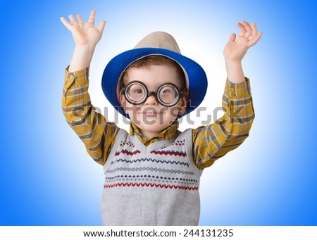 boy in a funny hat and glasses on blue background is happy closeup - stock photo