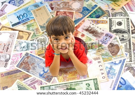 Boy in a hole in the middle of foreign money. - stock photo