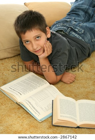 Boy in a room reading a book over a carpet.