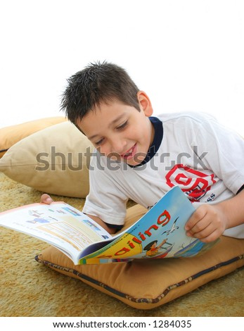 Boy in a room reading a book over a carpet. He is smiling and looks amused. Visit my gallery for more images of children - stock photo