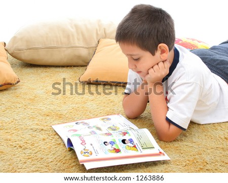 Boy in a room reading a book over a carpet. He looks interested and concentrated. Visit my gallery for more images of children - stock photo
