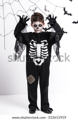 Boy in a skeleton costume, Halloween celebration, on the background of bats and cobwebs - stock photo