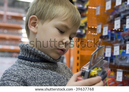 Boy in a store examine the toy - stock photo