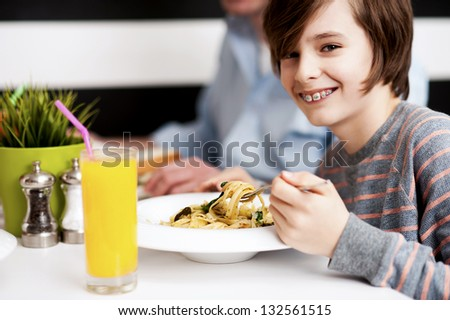 Boy in a striped t-shirt eating pasta with glass of fresh orange juice on table.