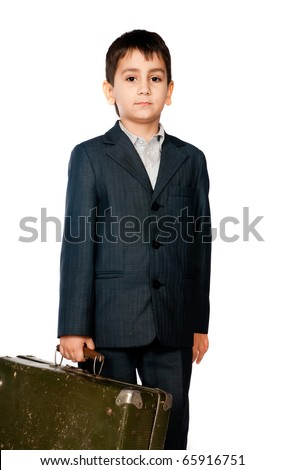 boy in a suit and carrying a suitcase on a light background - stock photo
