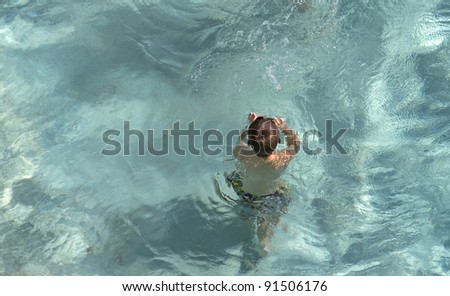Boy in a swimming pool with water eddying around him as seen from above