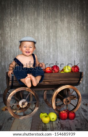 Boy in a trolley with apples - stock photo