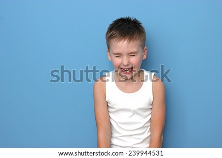 boy in a white sleeveless shirt screaming eyes closed hands down at the blue background horizontal view - stock photo