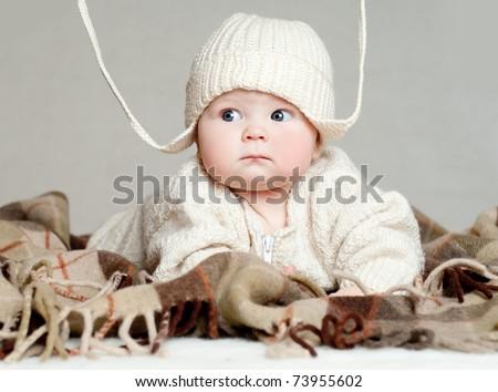 boy in a woolen cap on a warm plaid - stock photo
