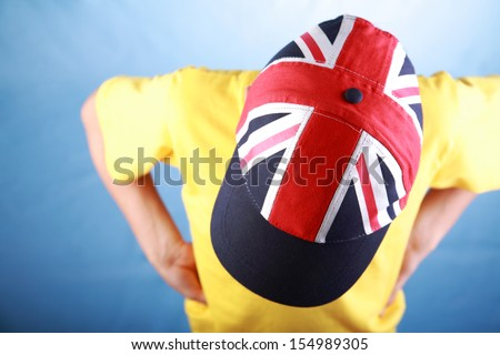 Boy in a yellow t-shirt wearing a baseball cap with a British national flag viewed from above  - stock photo