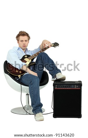 Boy in armchair with guitar and amp - stock photo