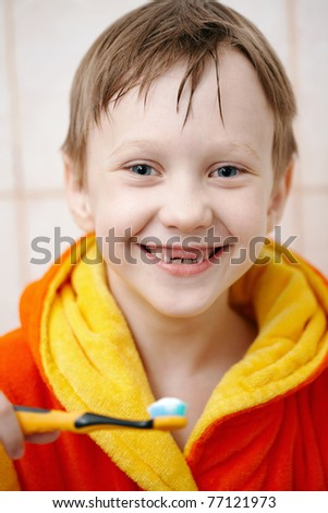 Boy in bathrobe hold of toothbrush and smiling/Brushing your teeth - stock photo