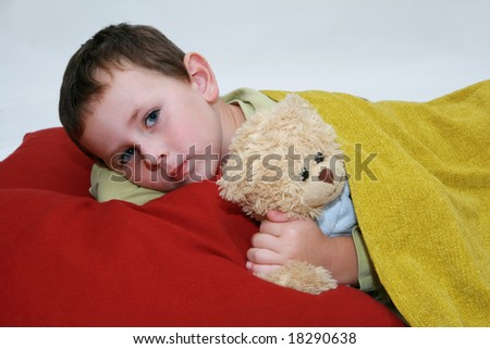 Boy in bed. Five years old boy lying in bed with teddy bear.