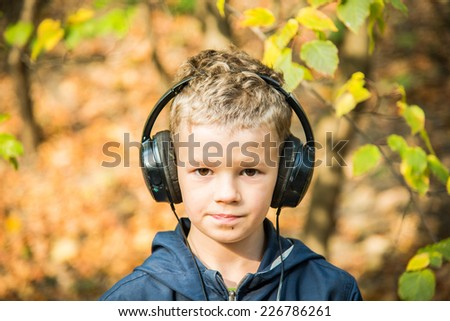Boy in big headphones listening to music - stock photo