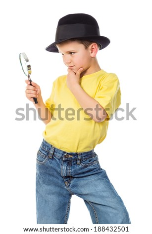 Boy in black hat standing with magnifying glass, isolated on white - stock photo
