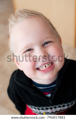 Boy In Black Shirt Smiling and Showing Teeth