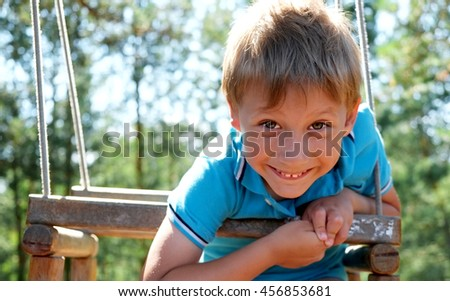 Boy in blue is swinging and smiling