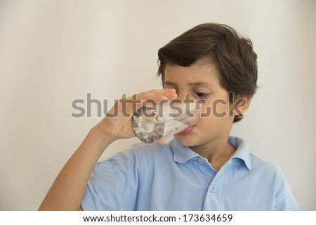 Boy in blue outfit drinking glass of water - stock photo