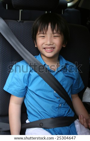 Boy in blue shirt fastening seat belt in the car - stock photo