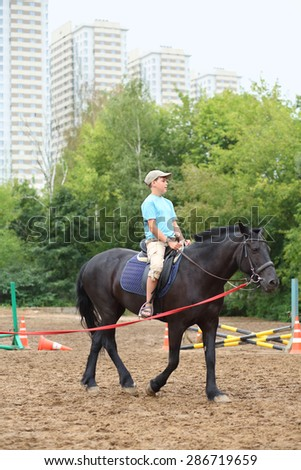 Boy in blue shirt riding a horse in park near the apartment complex - stock photo