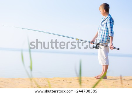 Boy in blue shirt standing on a pier with a fishing rod by the sea
