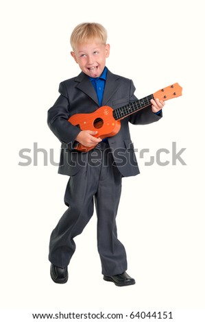 Boy in business suit having fun while playing a guitar - stock photo