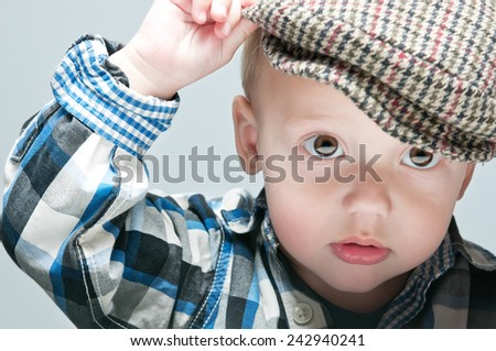 Boy in cap and checkered shirt on background - stock photo