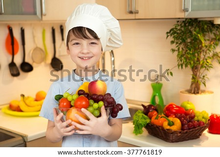 Boy in cap chef in the kitchen holding a bowl of vegetables and fruits and smiling. - stock photo