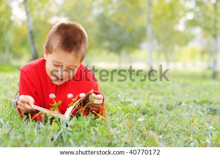 Boy in casual laying on grass reads funny book