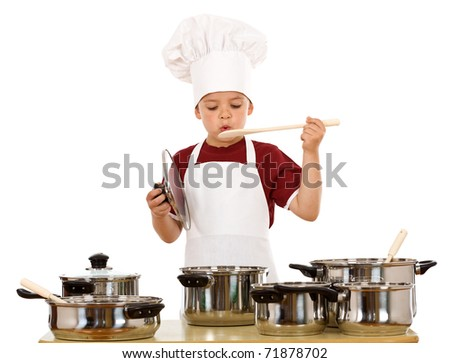 Boy in chef hat playing with cooking utensils - isolated - stock photo