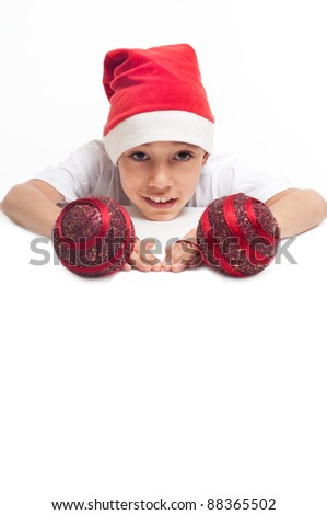 boy in christmas red hat holding red decorative balls with happy expression on his face with white copyspace to paste your advert or banner isolated on white background - stock photo