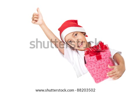 boy in christmas red hat showing thumbs up  gesture holding a gift box with happy expression on his face with white copyspace to paste your advert or banner isolated on white background - stock photo